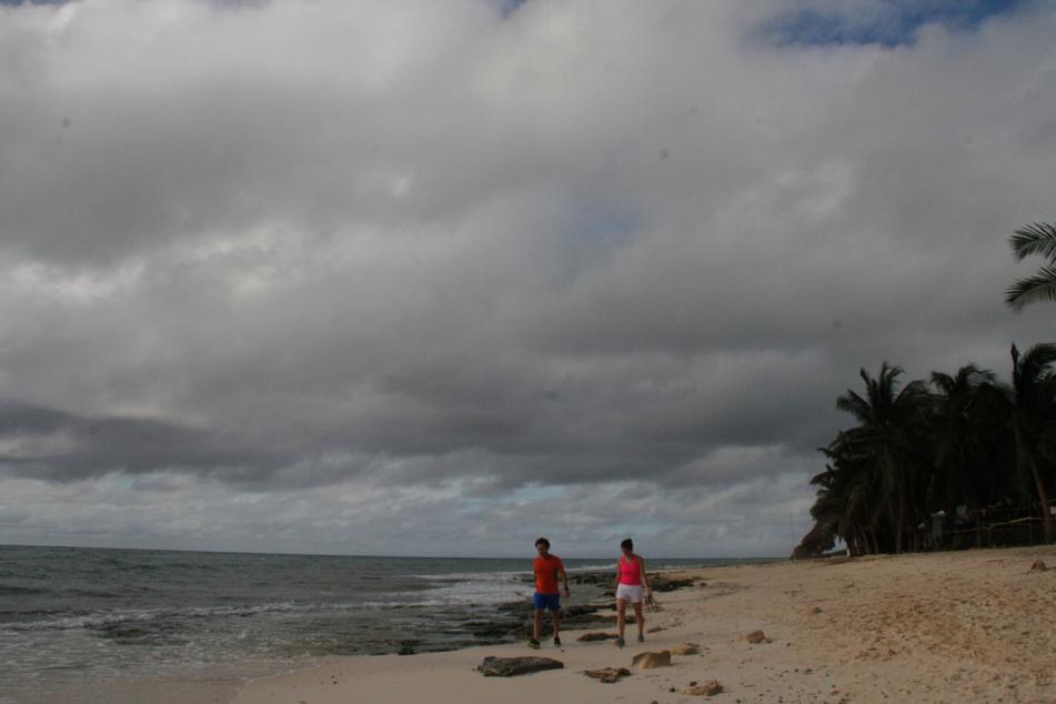 Ein Mann und eine Frau am Strand in der Nähe von Playa del Carmen. Hurrikan Delta verstärkte sich am Dienstag schnell zu einem Hurrikan der Kategorie zwei.