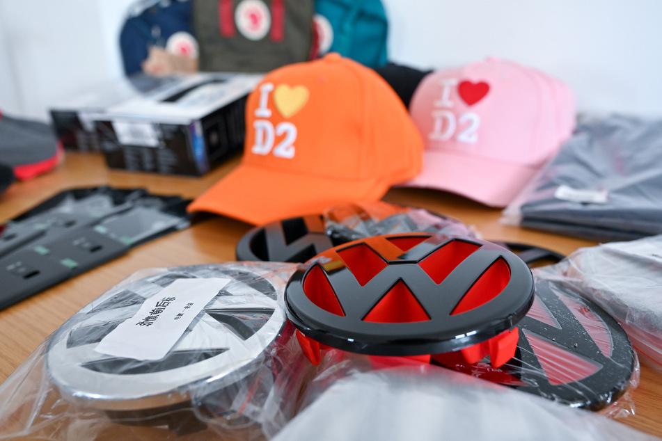 Nachgemachte Volkswagen-Logos und andere Fäschungen liegen im Zollamt am Flughafen Leipzig auf einem Tisch.