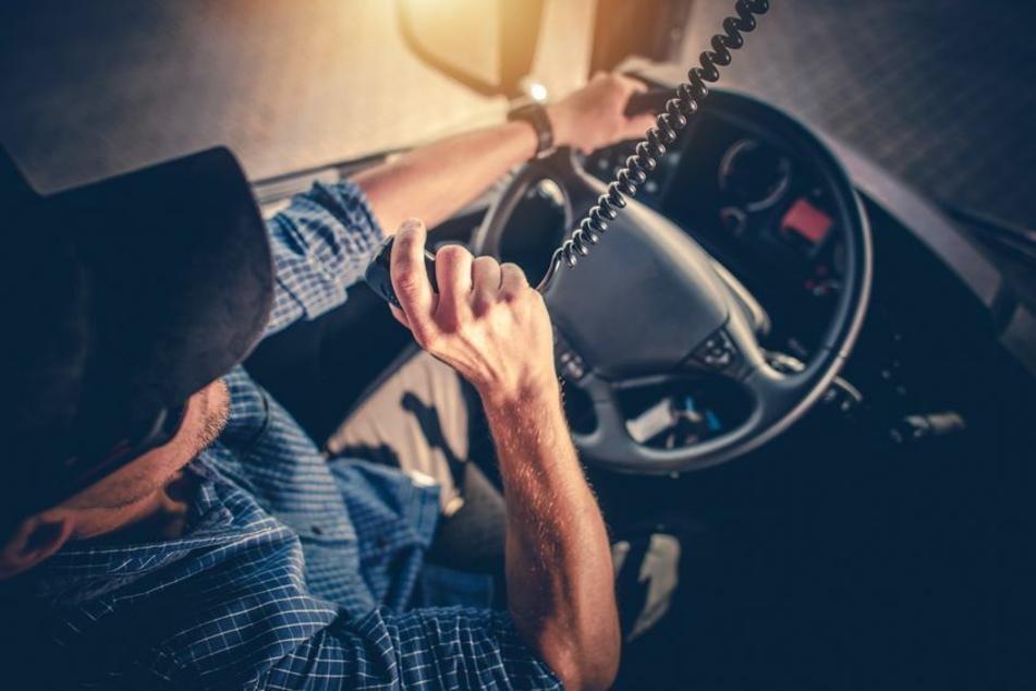 Ein Lkw-Fahrer spricht in sein Funkgerät. (Symbolbild)