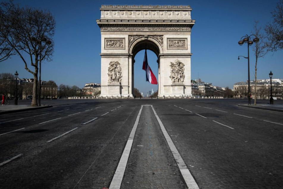 Frankreich, Paris: Die französische Flagge ist unter dem Arc de Triomphe zu sehen.