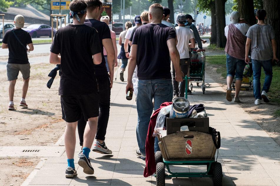 Mit einem Bollerwagen, einem Einkaufswagen und Bierflaschen in den Händen ziehen junge Leute am Vatertag durch Hannover.