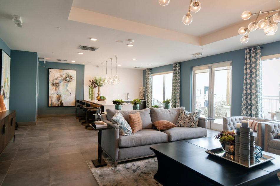 Das Sofa wirkt als Raumteiler, aber auch die Lichtquellen grenzen Ess- und Wohnbereich effektvoll voneinander ab.