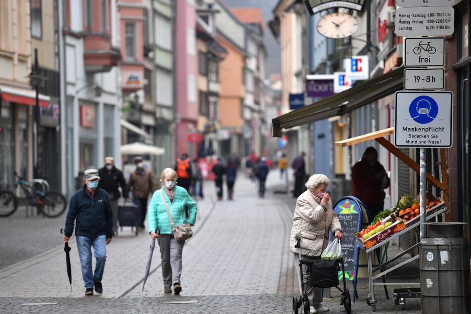 Menschen laufen mit einer Mund-Nasen-Bedeckung durch eine Thüringer Innenstadt. Mit einer Inzidenz von 135 bleibt der Freistaat das am stärksten betroffene Bundesland.