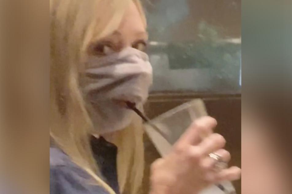Die unbekannte Frau hat einige Probleme dabei, mit den Strohlhalm den Schlitz in ihrer Maske zu treffen.