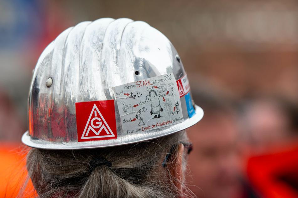 Das Logo der IG Metall auf dem Helm eines Stahlarbeiters zu sehen.