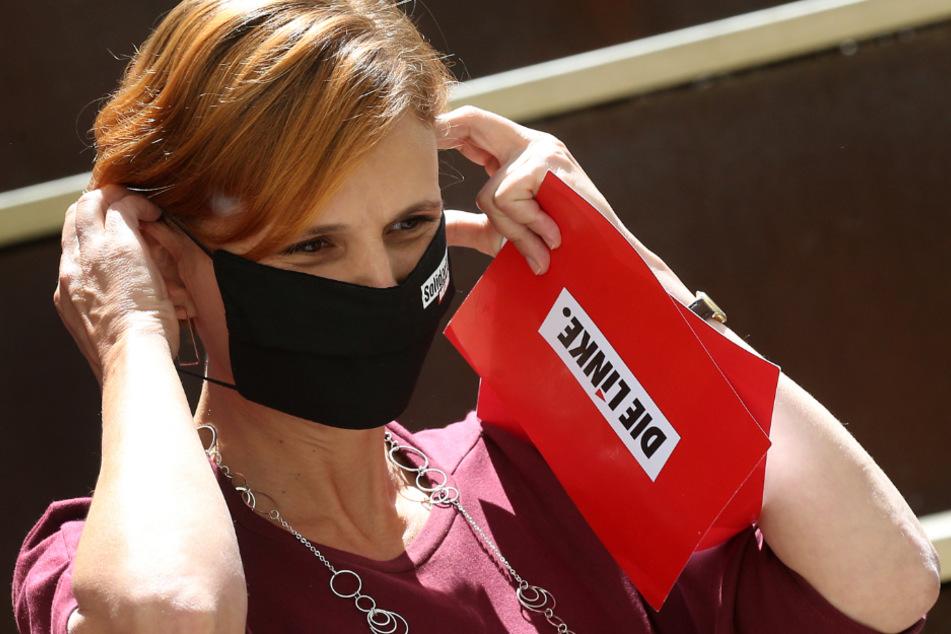 Katja Kipping setzt sich zu einer Pressekonferenz im Hof ihrer Parteizentrale eine Mund-Nasenschutzmaske auf.