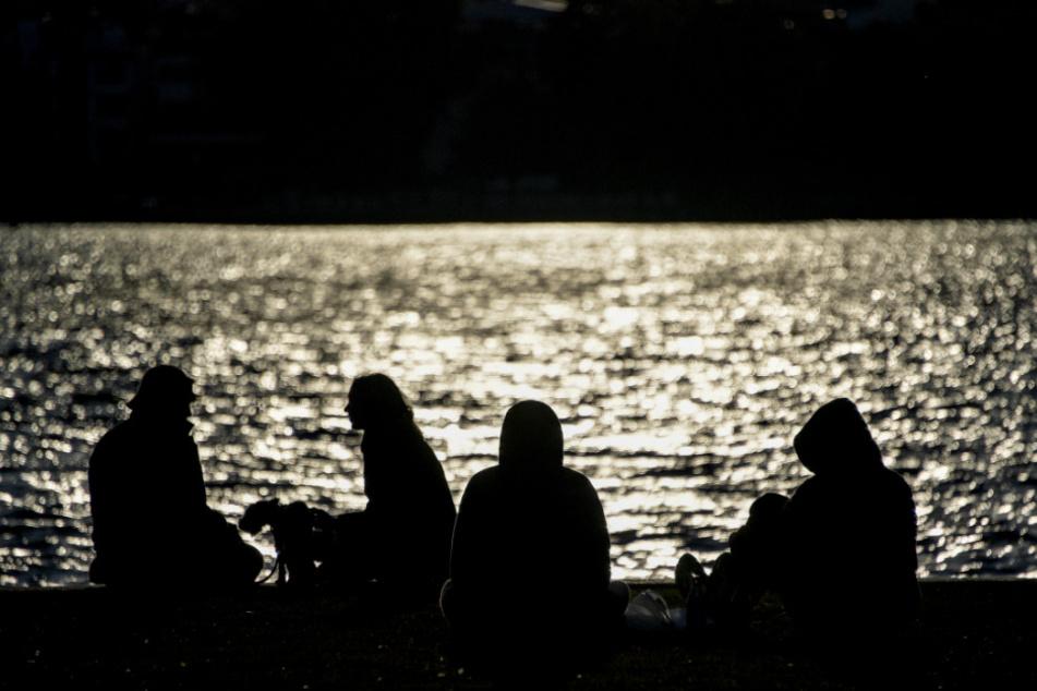Menschen sitzen um Ufer der Außenalster in der Abendsonne.