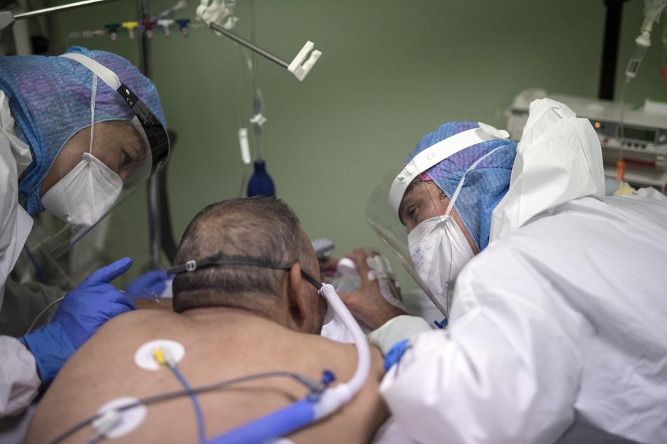 Medizinische Mitarbeiter in Schutzkleidung trösten einen COVID-19-Patienten auf der Intensivstation des Joseph-Imbert-Krankenhauses in Arles.
