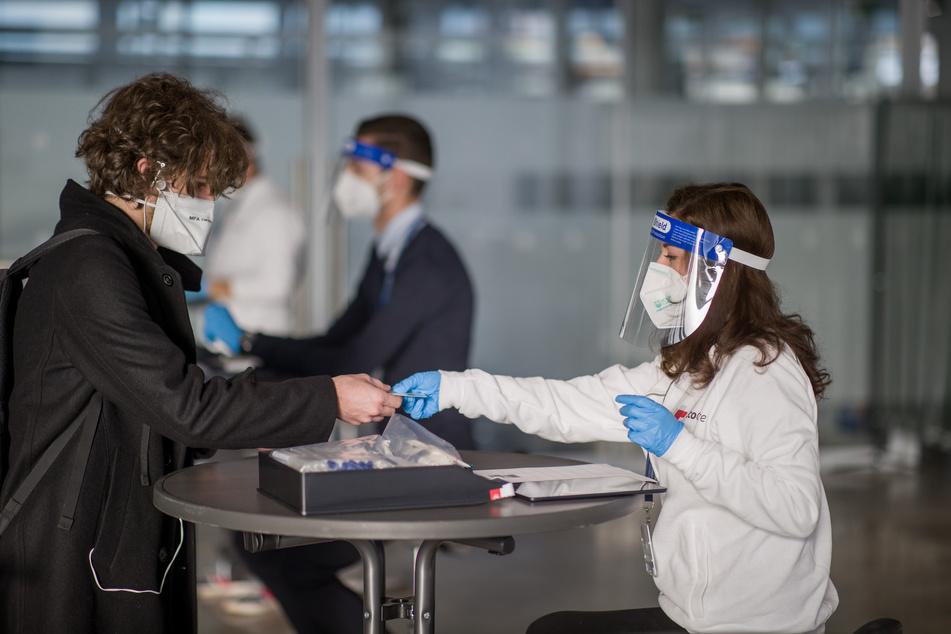 Bayern, Nürnberg: Eine Mitarbeiterin eines Corona Testzentrums nimmt am Nürnberger Flughafen die Personalien eines Reiserückkehrers aus Cluj in Rumänien, einem als Corona Risikogebiet eingestuften Land, für dessen Anmeldung zu einem Corona Test auf.