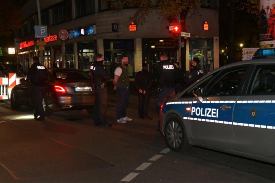 Einer der mutmaßlichen Dealer wurde von den Polizeibeamten festgenommen und steht auf der Straße. Im Hintergrund steht der Mietwagen.
