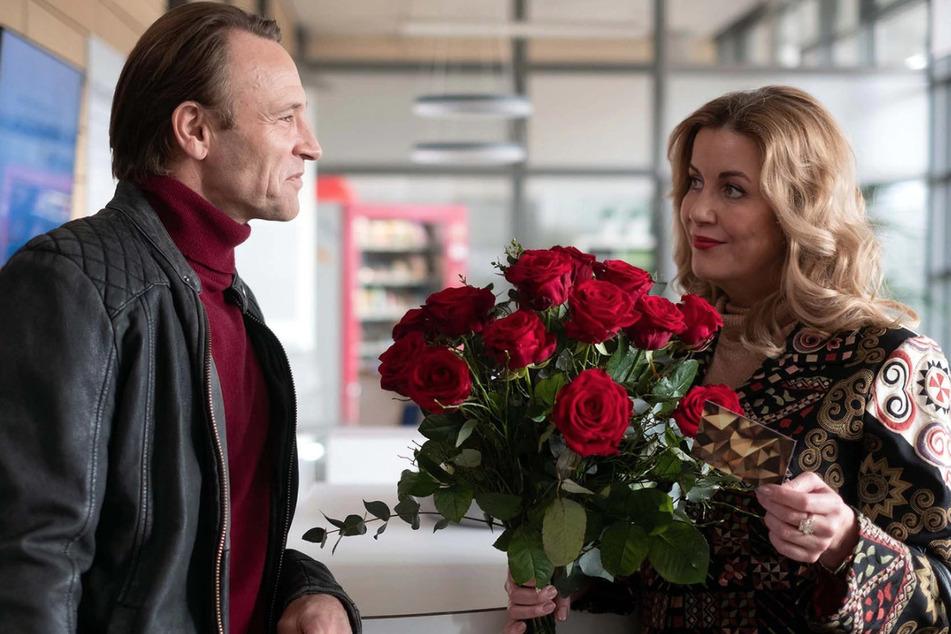 Sarah Marquardt bekommt einen Strauß Rosen geliefert. Dr. Martin Stein kann sich denken, wer der Absender ist.