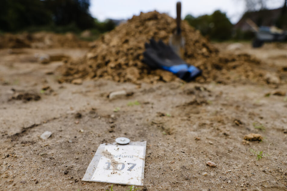 Ein Fundstück ist bei Ausgrabungen auf dem Boden markiert.