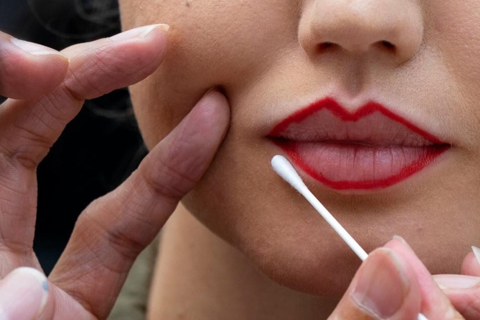 Lippen einer Frau werden geschminkt (Symbolbild). Den Traum von schönen Lippen hat die hübsche Britin noch nicht aufgegeben.