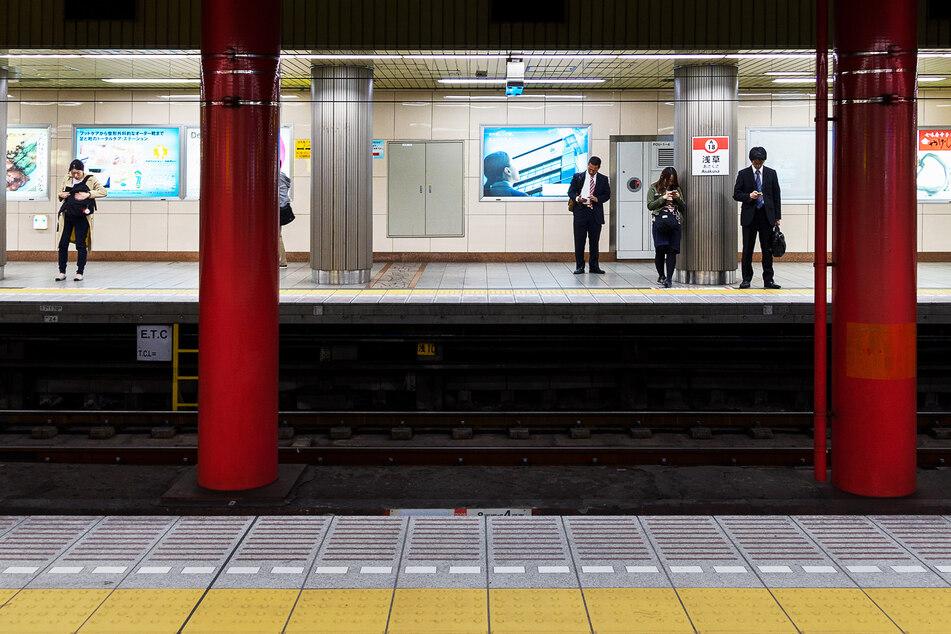 Etwa ein Meter Höhenunterschied gibt es an U-Bahnstationen in Tokio zwischen Bahnsteig und Gleisen. Züge rauschen vorbei.