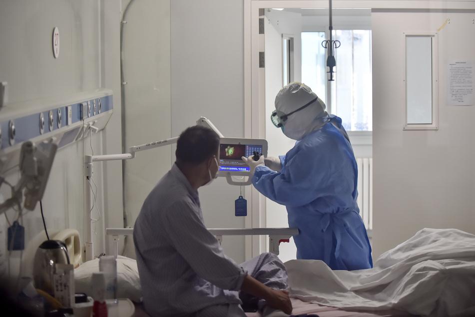 Eine Krankenschwester stellt für einen COVID-19-Patienten auf einer Isolierstation im Pekinger Ditan-Krankenhaus ein Fernsehgerät ein.