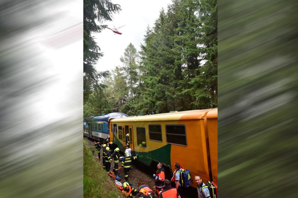 Rettungskräfte inspizieren am Unglücksort die Züge, die miteinander kollidiert sind.