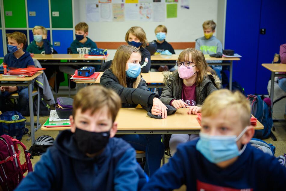Schülerinnen und Schüler sitzen mit einer Maske im Unterricht.