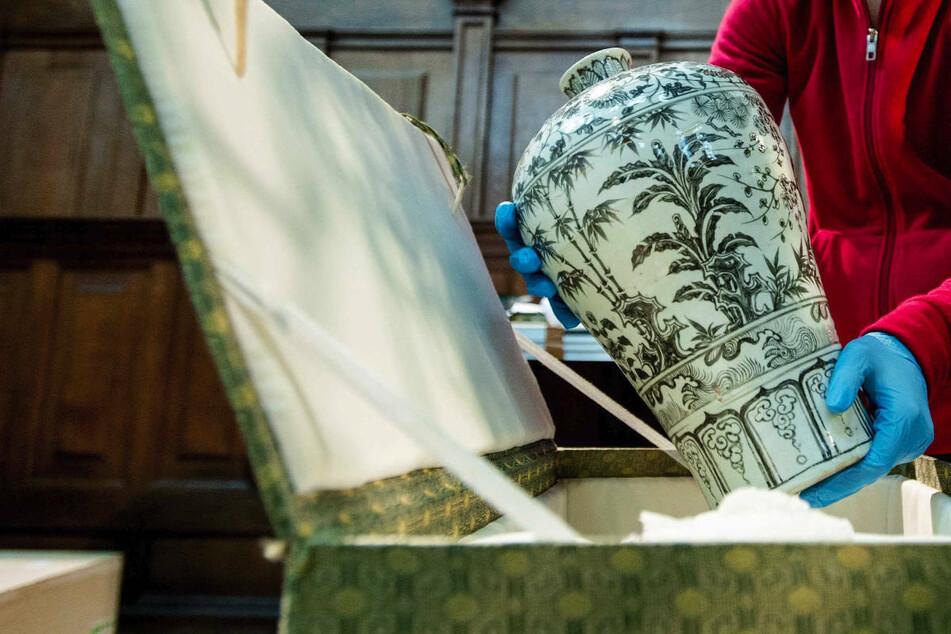 """Eine Mitarbeiterin der Nieuwe Kerk in Amsterdam hält eine Ming-Vase in der Hand. Das Berliner Arbeitsgericht hat am Dienstag die Kündigung einer Verkäuferin bestätigt, die ihre Chefin als """"Ming-Vase"""" bezeichnet hat. (Symbolfoto)"""