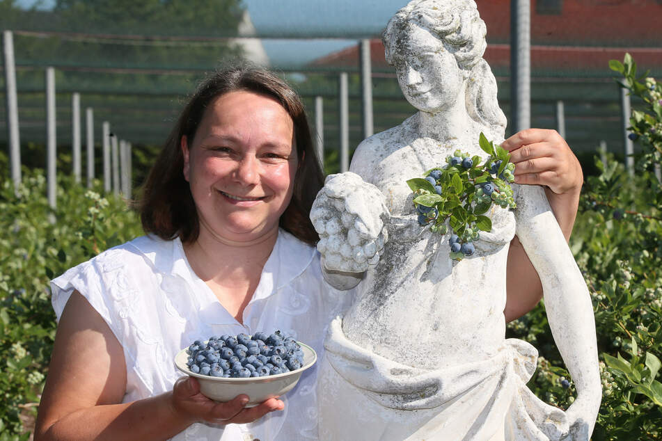 Das Erbstück soll für reiche Ernten sorgen: Sandra Lorenz (46) neben ihrer Heidelbeergöttin, die sie mitten in ihrer Plantage platziert hat.