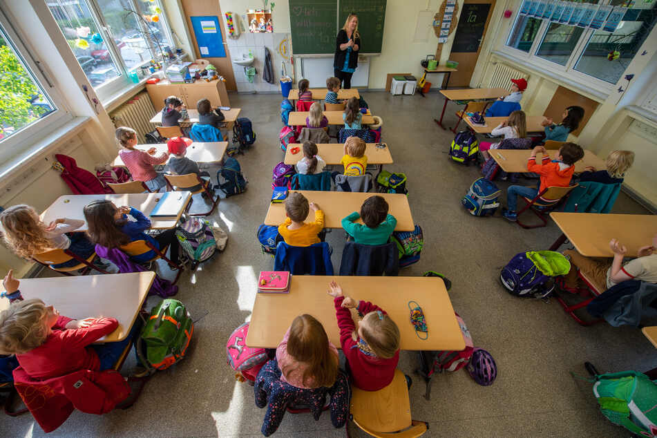Schüler einer ersten Grundschulklasse sitzen im Unterricht auf ihren Plätzen.