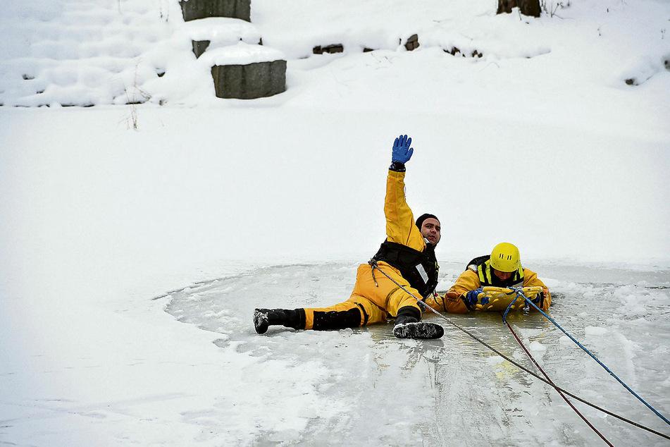Mithilfe eines sogenannten Spine-Boardes wird der eingebrochene Mann aus dem Teich gerettet.