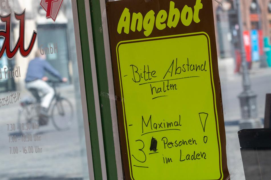 """Auf einem Zettel an einem Geschäft steht geschrieben: """"Bitte Abstand halten. Maximal 3 Personen im Laden!""""."""