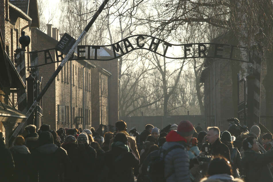 "Auschwitz concentration camp: People stand in front of the main gate inscribed with the slogan ""Arbeit macht frei"" (Work makes you free). Soviet troops Auschwitz on 27 January 1945."