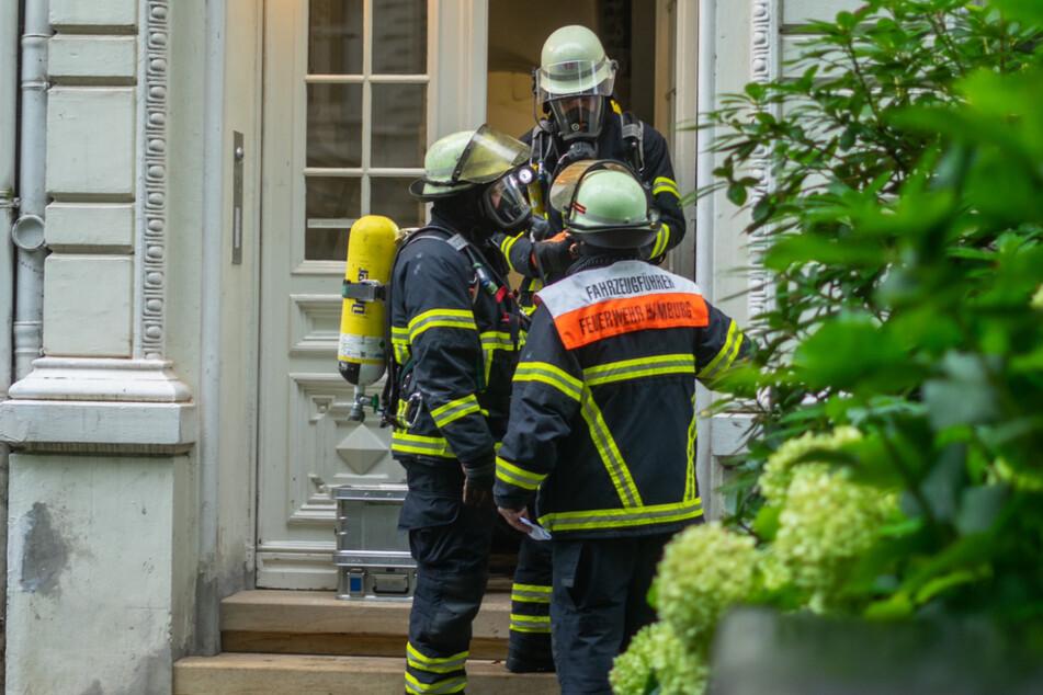 Einsatzkräfte stehen vor dem Haus in der Heimhuder Straße.
