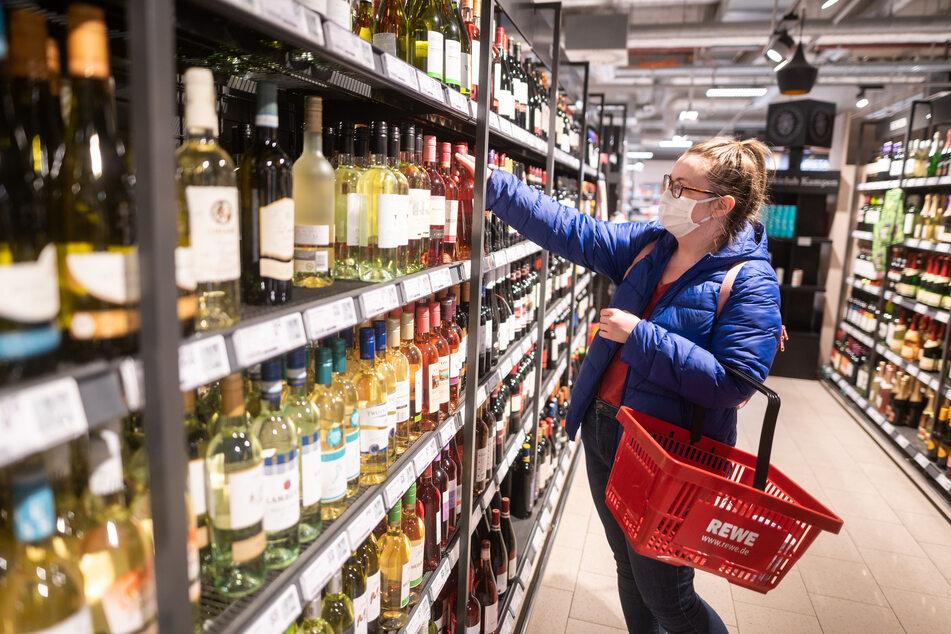 Eine Frau greift in einem Supermarkt nach einer Flasche Wein.