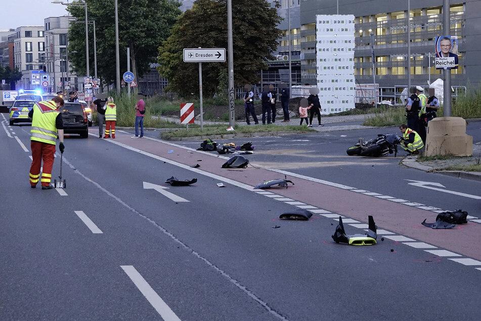 Teile des Motorrads liegen verstreut auf der Straße herum. Einsatzkräfte kümmern sich um die Aufräumarbeiten.