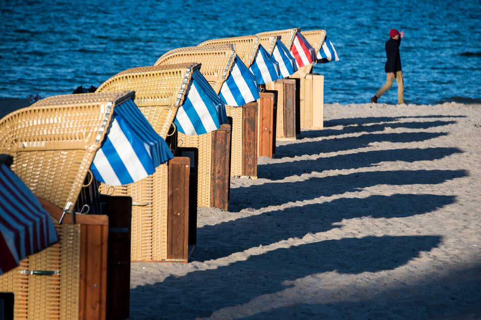Strandkörbe werfen am Abend lange Schatten auf den Strand an der Ostsee.