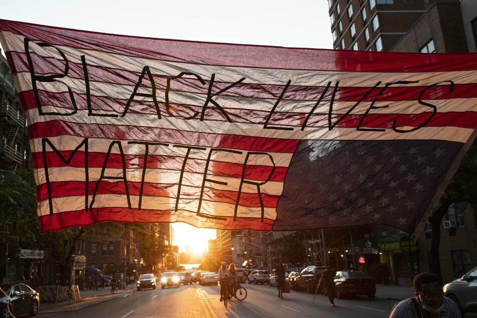 """Die Sonne geht unter hinter einer über eine Straße gespannte, umgedrehten US-Flagge bei einer friedliche, aber lautstarke Demonstrationen Mitte Juni der """"Black Lives Matter""""-Bewegung."""