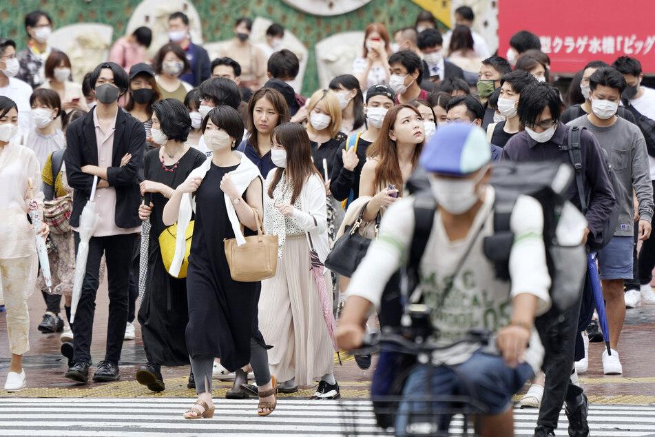 Passanten mit Mundschutzen gehen auf einer stark frequentierten Straße vor dem Bahnhof JR im Stadtteil Shibuya.