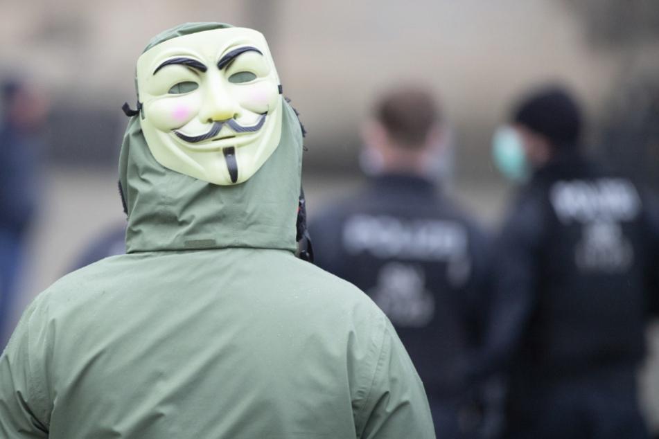"""Dresden: Eine Frau mit einer Guy-Fawkes-Maske steht hinter Polizisten. Zuvor hatten die sogenannten """"Corona-Rebellen"""" im Internet zu einer Demonstration aufgerufen."""