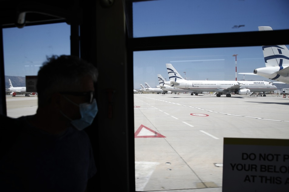 Ein Reisender mit Mundschutz sieht in Richtung geparkter Flugzeuge der Aegean Airlines auf dem Internationalen Flughafen Athen Eleftherios Venizelos an