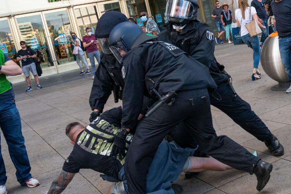 Polizisten halten bei einer Demonstration auf dem Alexanderplatz einen Mann fest.