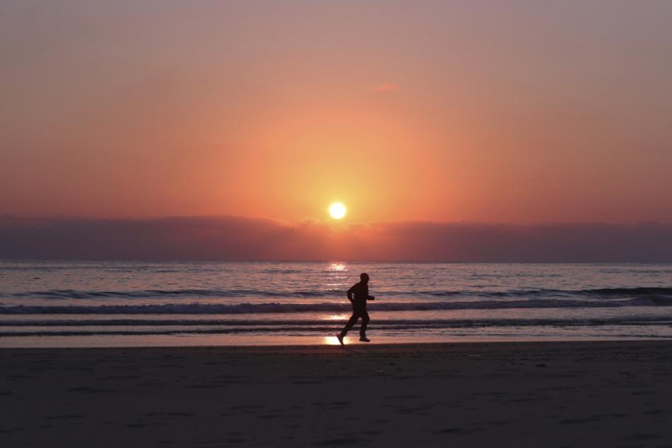 Libanon, Beirut: Ein Mann joggt am leeren Strand Ramlet al-Baida während der Ausgangsbeschränkungen zur Eindämmung des neuartigen Coronavirus.