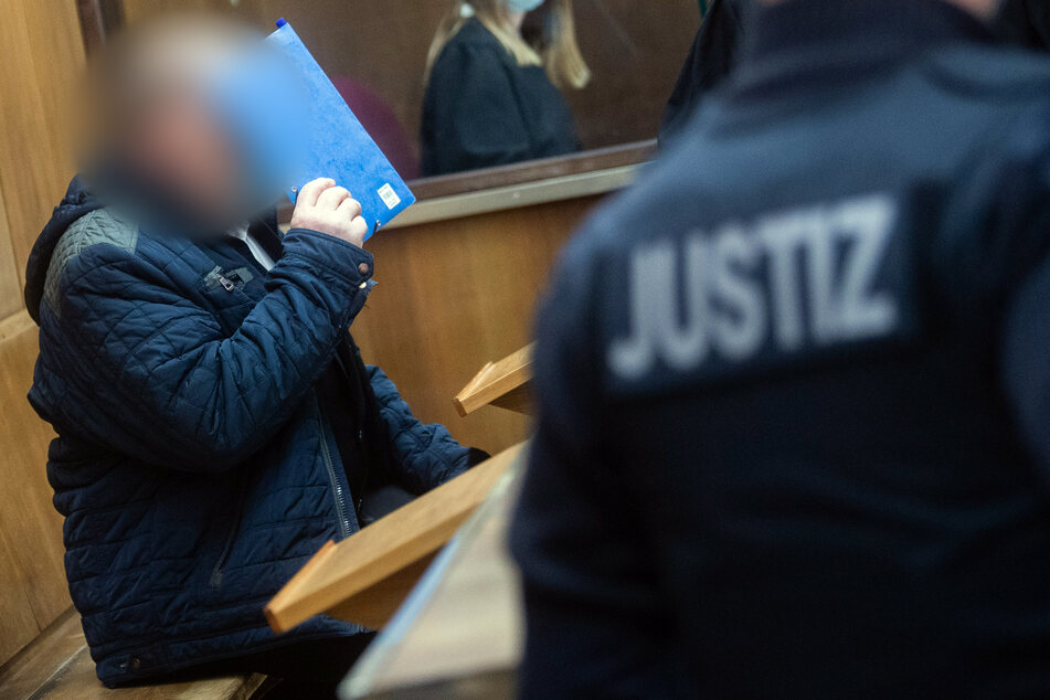 Der Angeklagte sitzt zum Prozessauftakt im Gerichtssaal des Landgerichtes Hannover und hält sich eine Mappe vor das Gesicht.
