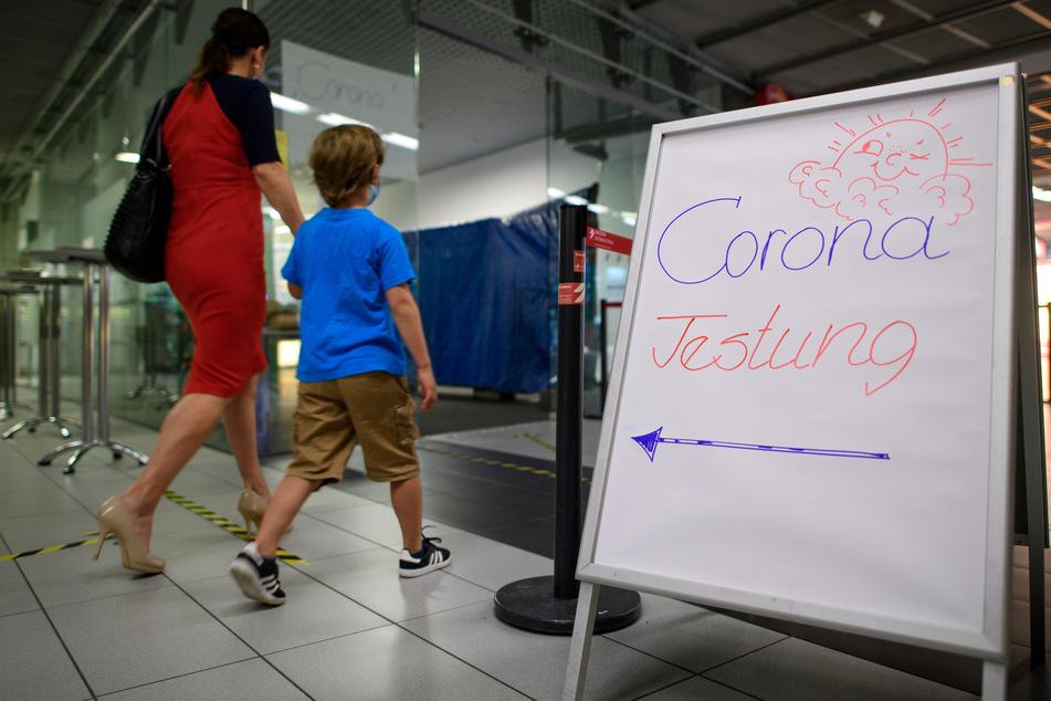 Eine Frau geht mit ihrem Sohn in die Corona-Teststation für Urlaubsrückkehrer am Flughafen Dresden International.