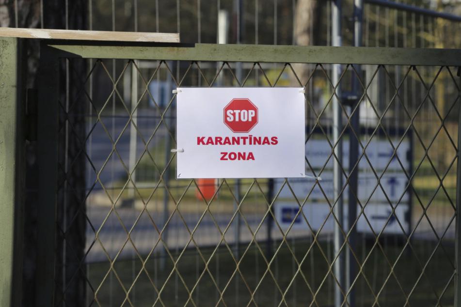 """Ein Schild mit einem Stoppzeichen und der Aufschrift """"Karantinas zona"""" (Quarantänezone) hängt an einem Zauntor neben der Teststation am Lettischen Zentrum für Infektiologie in Riga."""