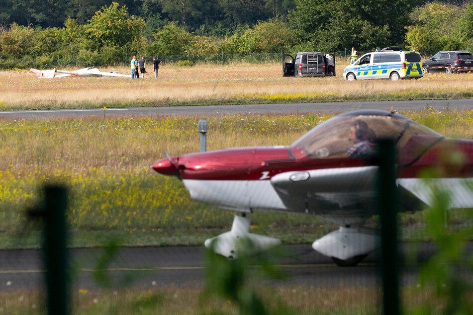 Ein abgestürztes Segelflugzeug liegt auf dem Flugplatz Hangelar bei Bonn, während im Vordergrund ein Sportflugzeug vorbeirollt.