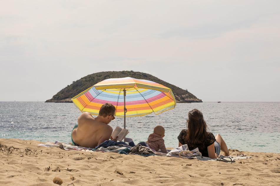 Spanien, Magaluf: Eine Familie liegt unter einem Sonnenschirm am fast leeren Strand von Magaluf auf Mallorca. Der große Ansturm auf die Insel blieb trotz Lockdown-Ende aus.