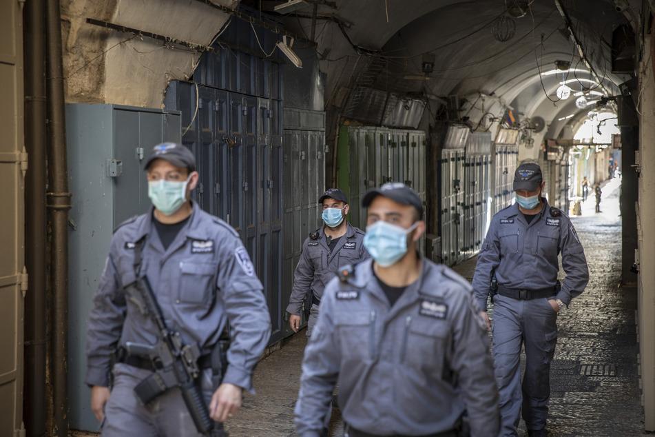 Israelische Polizisten mit Mundschutz patrouillieren in der Altstadt von Jerusalem.