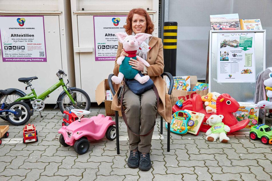 Monica Lierhaus, Moderatorin, sitzt auf dem Recyclinghof Liebigstraße in Hamburg-Billbrook vor diversen Spielsachen.