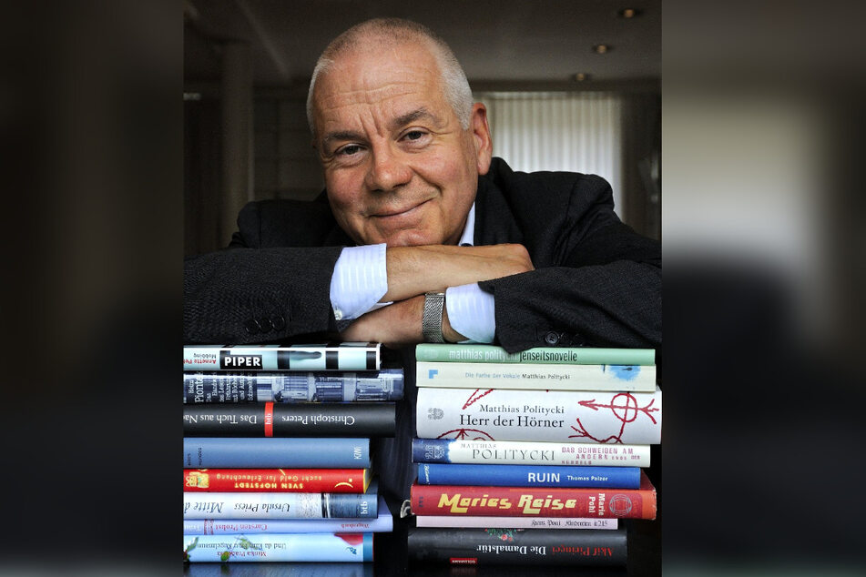Der Schriftsteller Matthias Politycki (66) lehnt sich auf einen Stapel Bücher. Er lebt inzwischen in Wien.