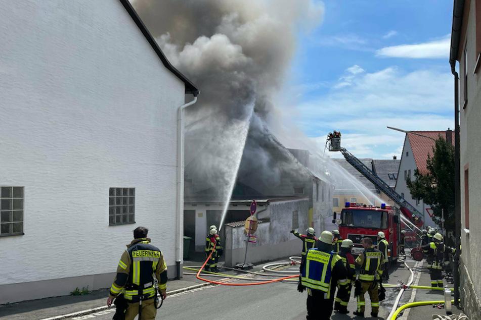 Einsatzkräfte der Feuerwehr kämpfen gegen den Dachstuhlbrand in Thiersheim.