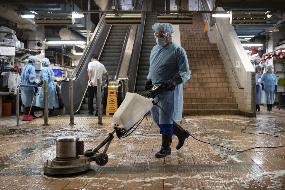 Mitarbeiter der Umwelt- und Lebensmittelhygiene in Schutzkleidung desinfizieren einen sogenannten Nassmarkt in Honkong.