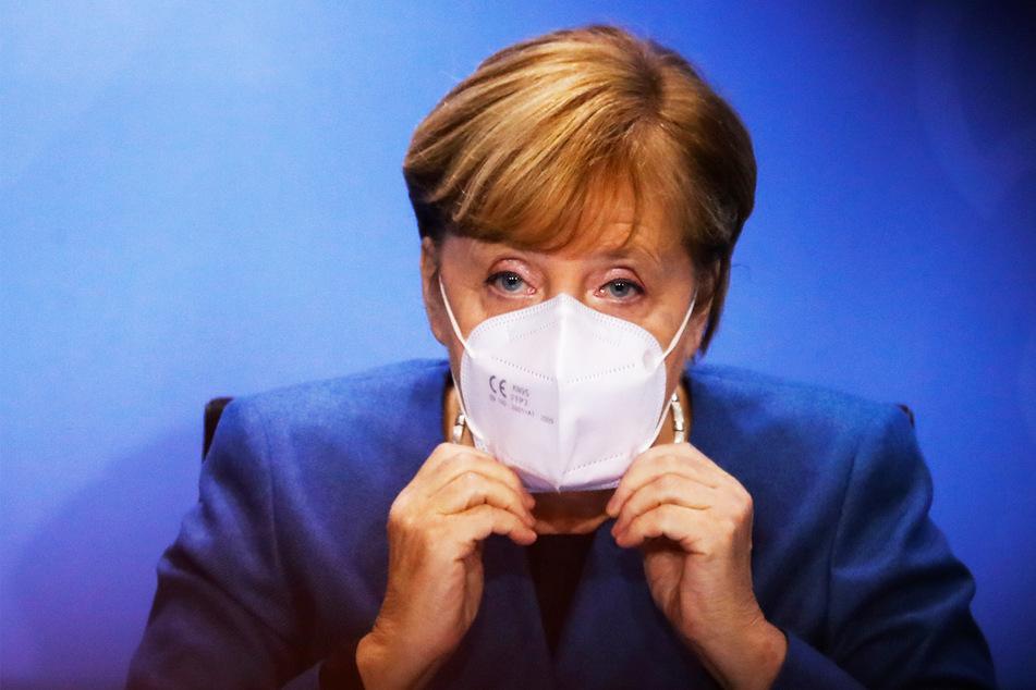 Bundeskanzlerin Angela Merkel (66) setzt ihre Gesichtsmaske auf am Ende einer Pressekonferenz im Kanzleramt nach einem Treffen mit den Ministerpräsidenten der Länder zum weiteren Vorgehen in der Corona-Pandemie.