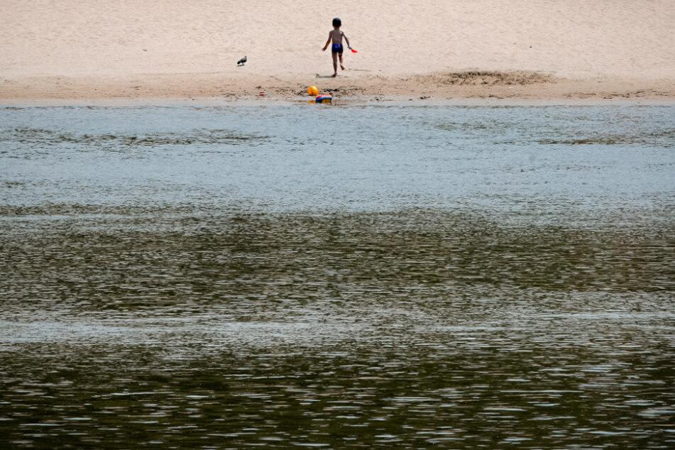 Rumänien, Calarasi: Ein kleines Kind läuft an einem Strand am Ufer der Donau.