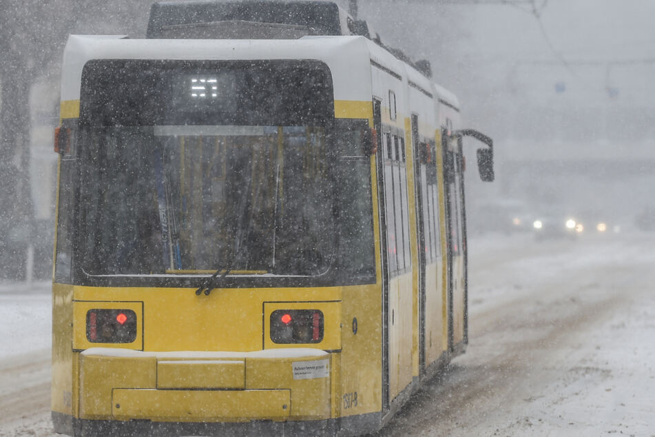 Eine Straßenbahn fährt auf der Bölschestraße in Berlin Friedrichshagen durch den Schnee.